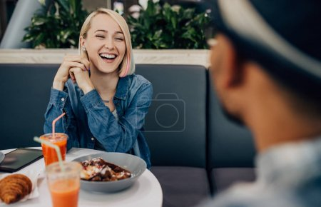 Photo for Happy young female laughing at funny story while communicating with ethnic guy during date in cafe - Royalty Free Image