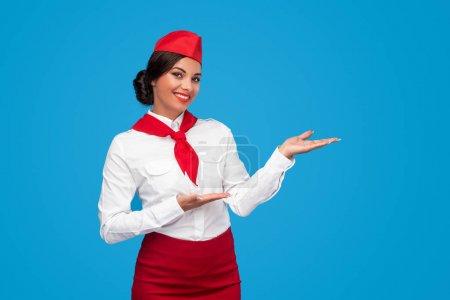 Photo pour Femme amicale en uniforme hôtesse de l'air souriant et regardant la caméra pendant la présentation de la compagnie aérienne sur fond bleu - image libre de droit