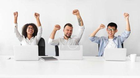 Photo pour Joyeux collègues divers hurlant d'excitation et levant des poings serrés tout en célébrant la victoire au travail - image libre de droit