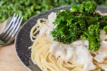 Pasta with kale, chicken in white sauce and spaghetti. Balanced meal. Healthy eating