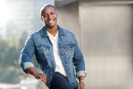 Photo for Portrait lifestyle head shot of an african american male in a blue jean jacket on a city urban rooftop, nice smile - Royalty Free Image