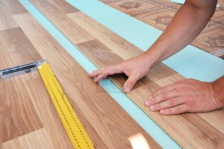Man laying laminate flooring. Installing wooden laminate flooring. Step by Step.