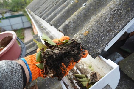 Rain Gutter Cleaning. Scooping leaves from gutter. Clean and Repair  Rain Gutters and Downspout with roofer hands. Step by Step.