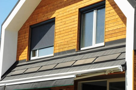 Close up on House Blinds Sun Protection Exterior with Solar Panels. Windows in New Modern Passive House Attic Facade Wooden Wall with Shutters Closed and Opened Outdoors.