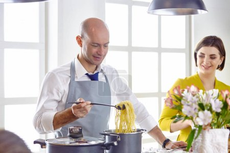 Photo for Attractive couple in love cooking and opens the wine in the kitchen while they cook dinner for a romantic evening - Royalty Free Image