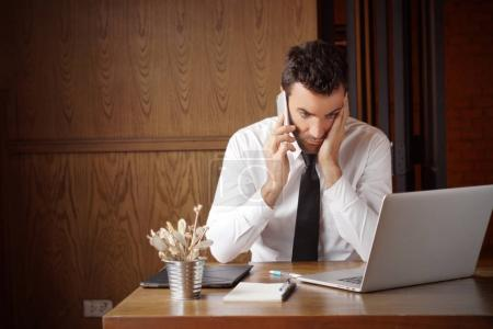 Businessman stressed out while dealing with problem, calling someone and look and computer screen. Can be used for illustration of article about, trading, internet problem, disappoint with service. Stock photo