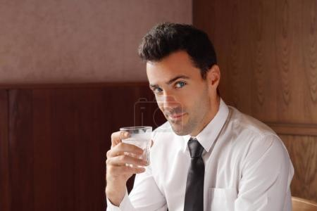 Good looking businessman holding a glass of water and smile.Water is key for anti aging concept. Stock photo