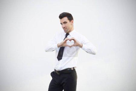Photo pour Homme d'affaires faisant un cœur avec ses mains sur fond blanc - image libre de droit
