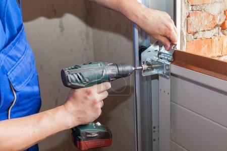 Montage von Garagentoren. Arbeiter installieren Hebesystem in Metallprofil mit Schraubenzieher.