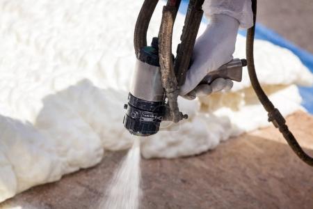 Foto de Técnico pulverización de aislamiento de espuma utilizando Plural componente pistola de pulverización - Imagen libre de derechos