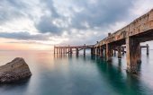 Old pier bridge in beautiful morning sunrise and calmness seascape