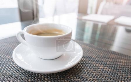 Photo pour Tasse blanche de café chaud sur la table avec lever du soleil le matin dans le temps de détente - image libre de droit