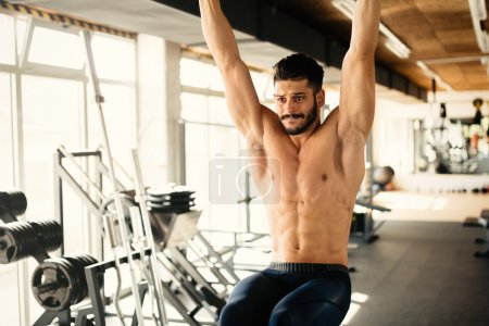 Photo for Abs workout by handsome man in gym - Royalty Free Image