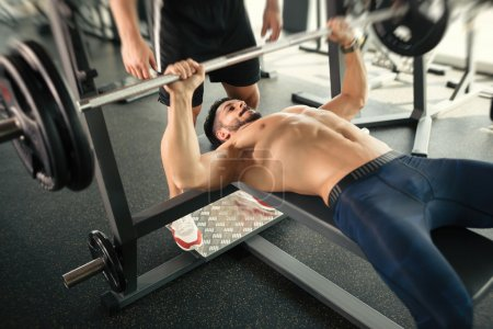 Photo for Handsome Muscular bodybuilder bench press workout in gym - Royalty Free Image
