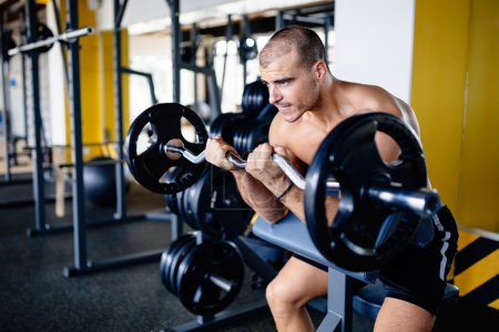 Strong ripped man training in gym