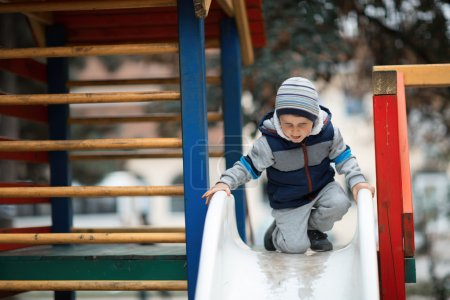 Photo pour Enfant grimpant le toboggan à l'extérieur - image libre de droit