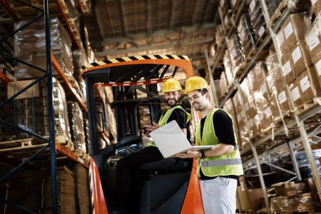 Workers using technology forklift in warehouse
