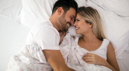 Photo pour Couple romantique au lit en souriant de la lingerie de nuit - image libre de droit