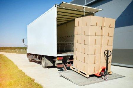 Photo pour Camion transport de marchandises emballées dans des boîtes d'entrepôt - image libre de droit