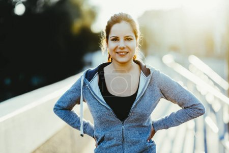 Beautiful sportswoman smiling in sunshine