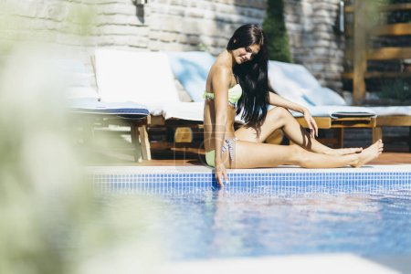 Beautiful young woman sunbathing at the poolside