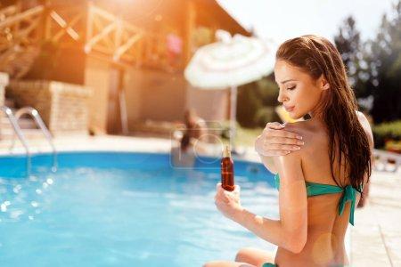 Woman applying sun lotion