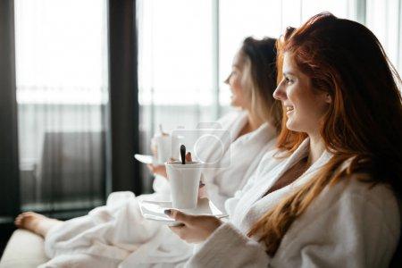Photo pour Femmes se détendre et boire du thé en peignoirs pendant le week-end bien-être - image libre de droit