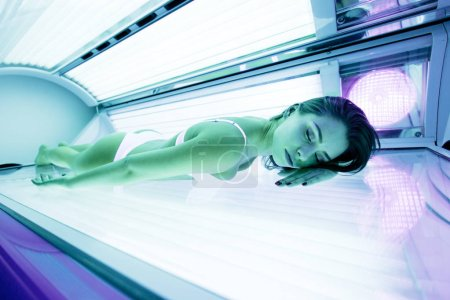 Beautiful brunette sunbathing in solarium