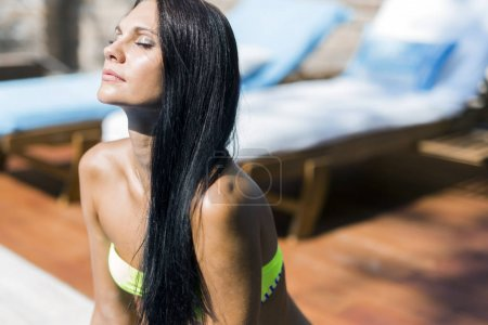 Woman with closed eyes sunbathing