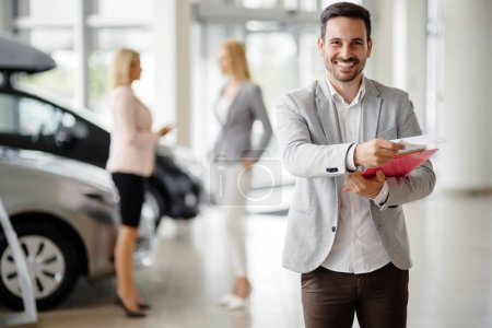 Photo for Salesperson at car dealership selling vehichles - Royalty Free Image