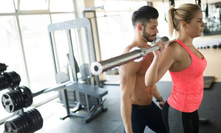 Personal trainer assisting woman