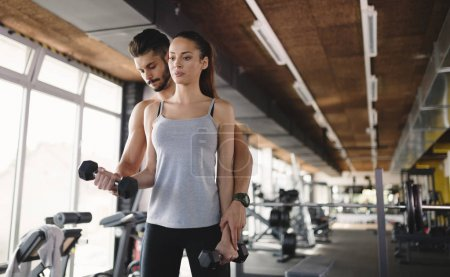 Personal trainer helping woman