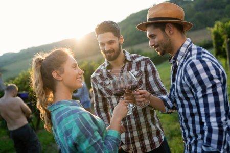 Happy people tasting wine in vineyard...