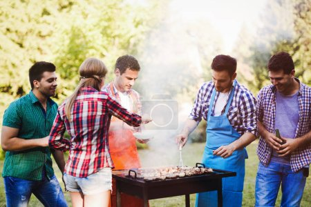 Happy friends enjoying barbecue party