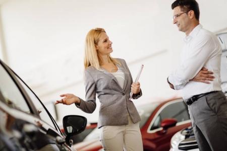 beautiful blonde woman selling cars