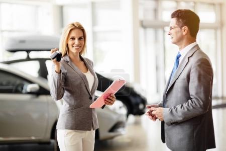 Saleswoman giving key of car