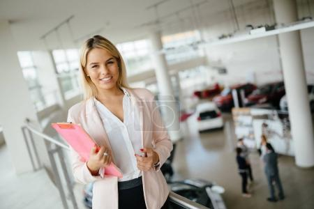 beautiful blonde woman at car dealership