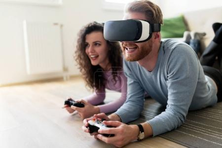 Photo for Happy young couple playing video games with virtual reality headsets at home - Royalty Free Image