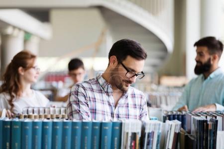 Photo pour Groupe de collégiens étudiant à la bibliothèque - image libre de droit