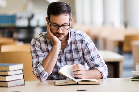 Libro de lectura del estudiante hombre serio en la biblioteca de la Universidad