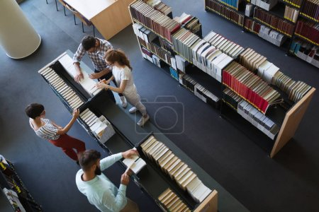 Group of college students studying at library