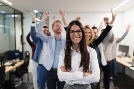 Successful team of young perspective businesspeople posing in office