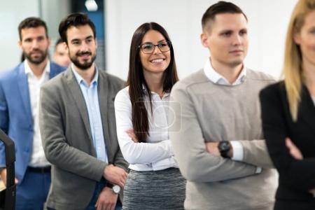 Photo pour Équipe réussie de jeunes gens d'affaires de perspective posant dans le bureau - image libre de droit