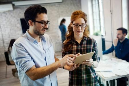 Picture of young perspective designers using tablet in office