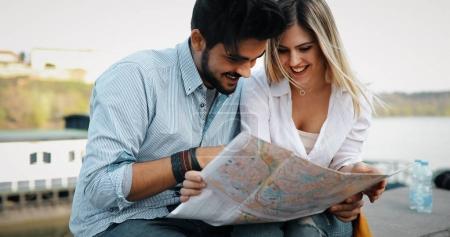 Photo pour Couple touriste souriant amoureux voyageant avec carte en plein air - image libre de droit