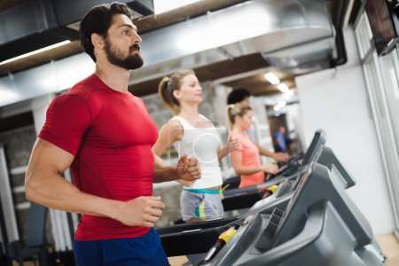 Young handsome man doing cardio training on treadmill in gym