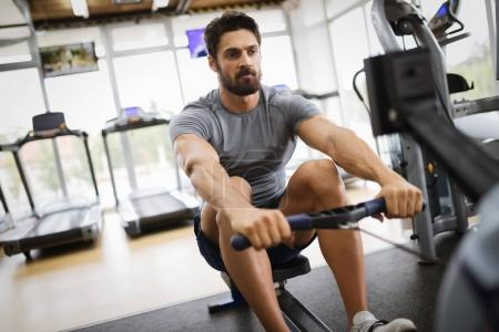 Young handsome man doing exercises in gym on rowing machine