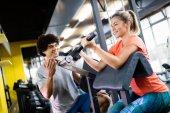 Personal trainer helping woman reach goals in gym