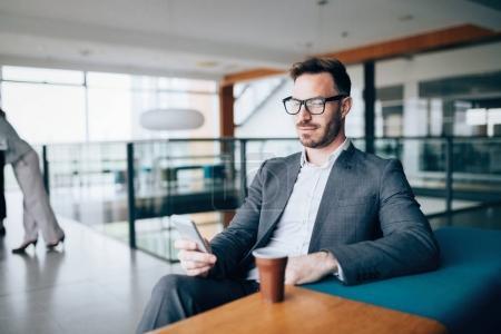 Photo pour Pensif jeune homme d'affaires en chemise dans le café en utilisant le téléphone - image libre de droit