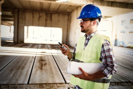 Male architect communicating on walkie-talkie at building site